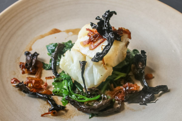 Skrei cod with wilted lambsquarters, caramelized shallots and black trumpet mushrooms