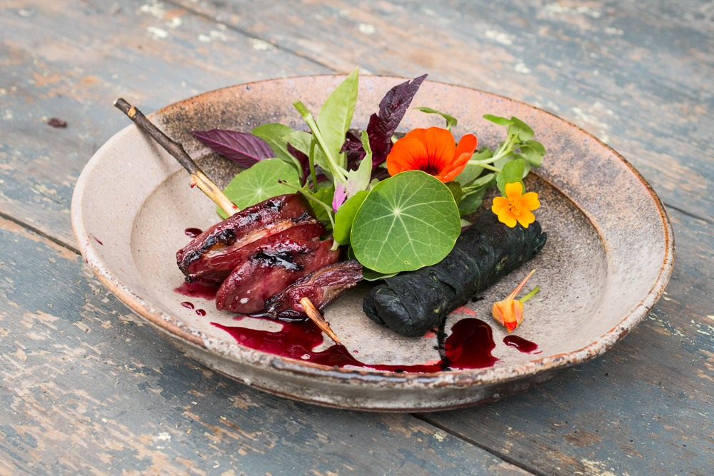 Smoked pigeon brochette with sunflower rolls, wild cherry sauce and foraged greens