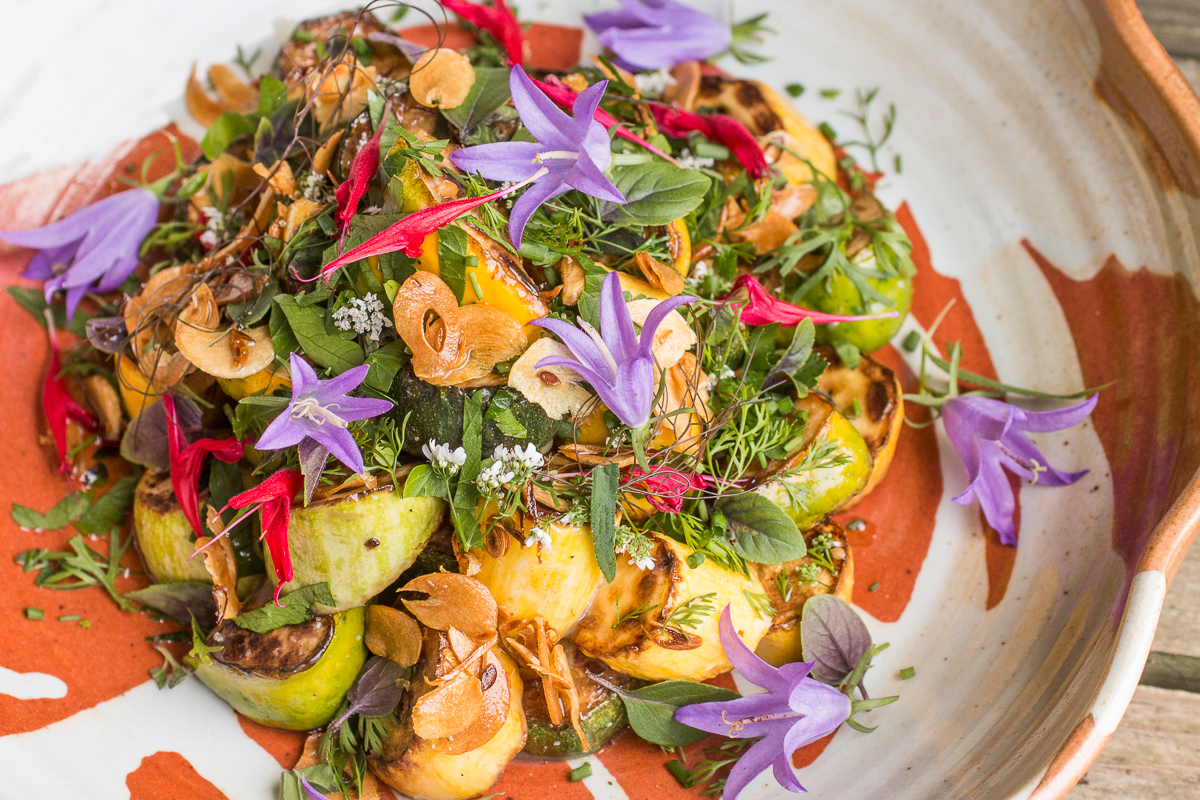 Summer squash salad with edible creeping bellflowers and garden herbs
