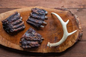 cooked venison or deer ribs with antlers on a board